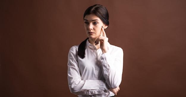 Portret van een ernstige donkerbruine onderneemster die met haar vinger aan haar gezicht denkt