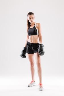 Portret van een ernstige gemotiveerde vrouw in bokshandschoenen status