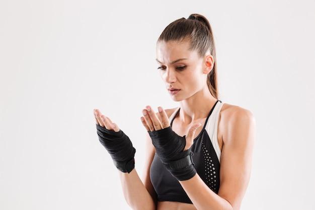 Portret van een ernstige gerichte sportvrouw die handverbanden draagt