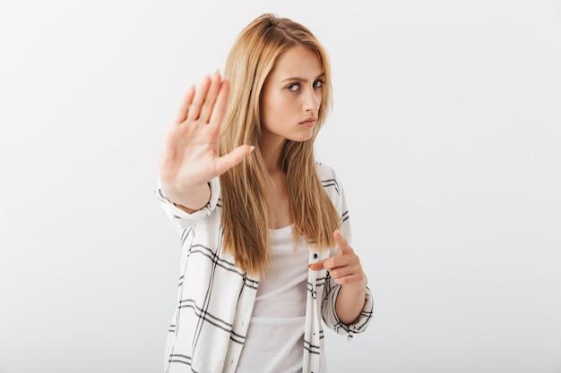 Portret van een ernstige jonge toevallige vrouw die stop toont