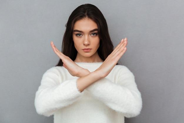 Portret van een ernstige jonge vrouw die gekruist handengebaar toont