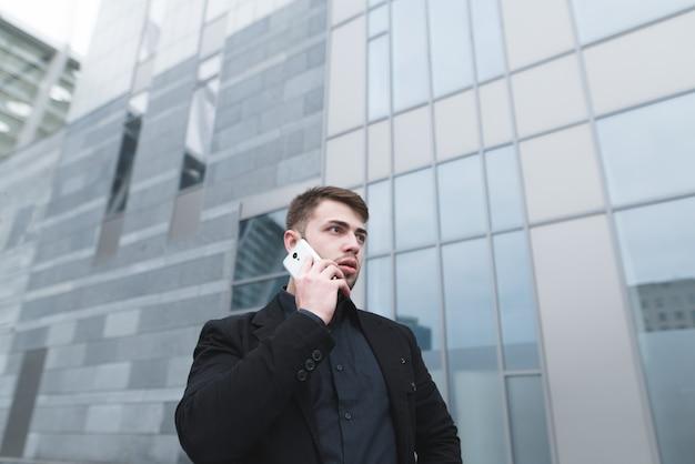 Portret van een ernstige jonge zakenman met een baard die telefonisch spreekt over moderne landbouw.