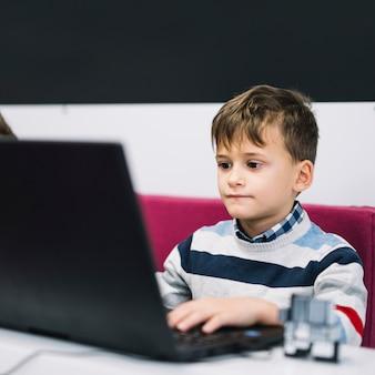 Portret van een ernstige jongen die laptop in het klaslokaal met behulp van