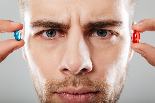 Portret van een ernstige man die twee capsules houdt