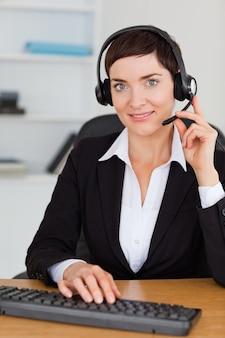 Portret van een ernstige secretaresse die met een hoofdtelefoon roept