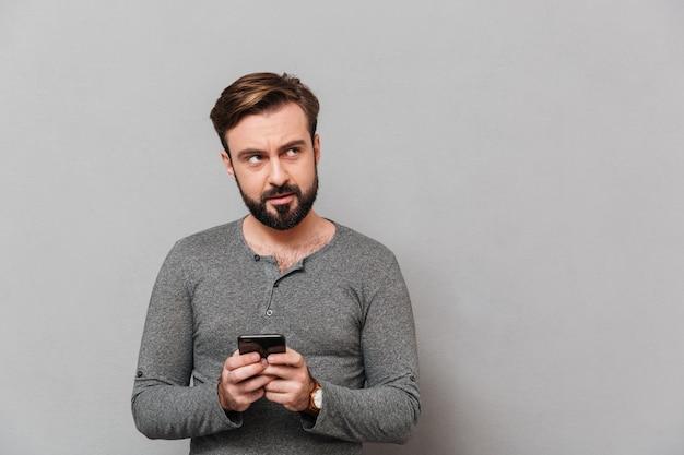 Portret van een ernstige toevallige mens die mobiele telefoon houdt