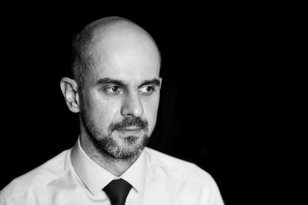 Portret van een ernstige trieste kale man, zwart-wit foto op een zwarte achtergrond