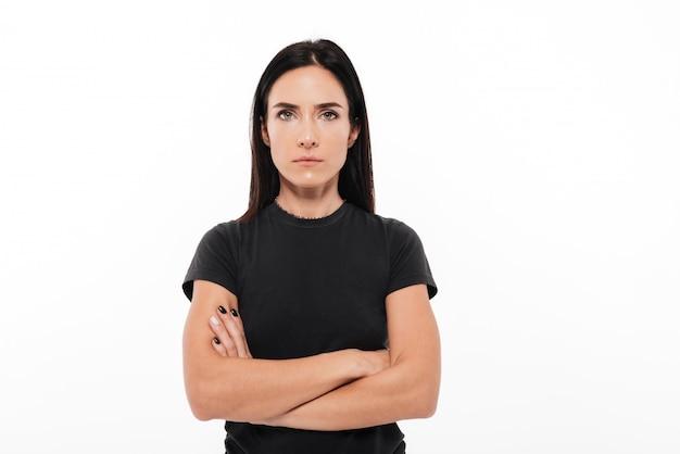 Portret van een ernstige vrouw die zich met gevouwen wapens bevindt