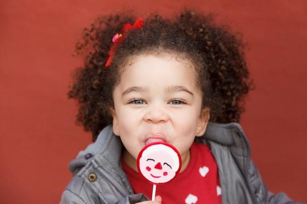 Portret van een etnisch meisje dat een lolly houdt