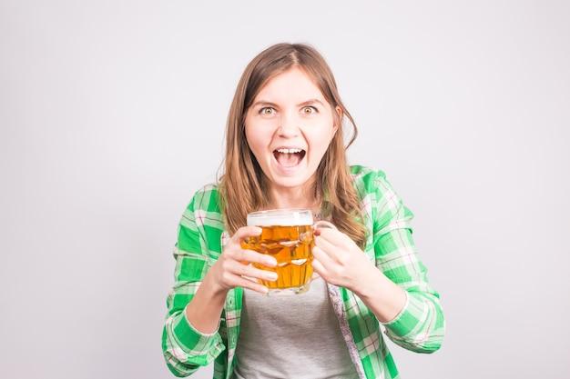Portret van een euforische sportfan die een bierflesje vasthoudt. vrouw met bier.