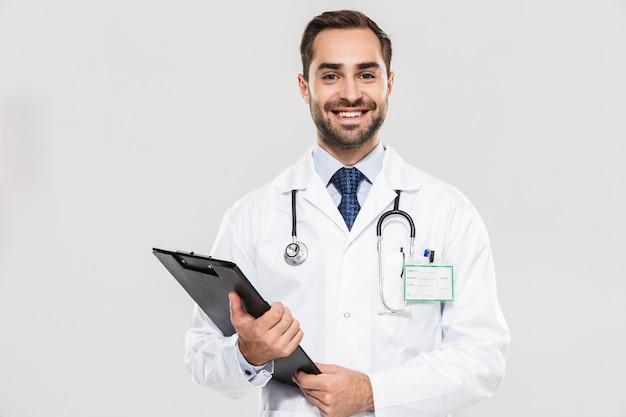 Portret van een europese jonge arts die lacht en een gezondheidskaart vasthoudt die over een witte muur wordt geïsoleerd