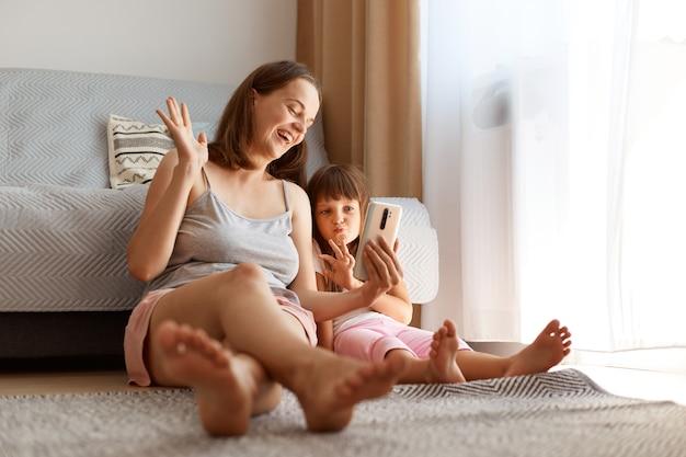 Portret van een extreem gelukkige moederblogger die met haar dochter livestream uitzendt, hand zwaait naar volgers, positieve emoties uitdrukt, vrolijk lacht.