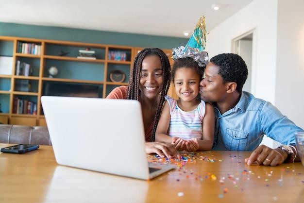 Portret van een familie die de verjaardag online viert tijdens een videogesprek met familie en vrienden terwijl ze thuis blijft