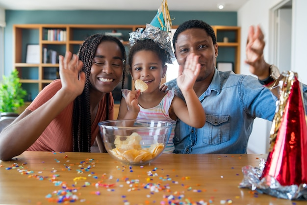 Portret van een familie die de verjaardag online viert tijdens een videogesprek terwijl ze thuis blijft