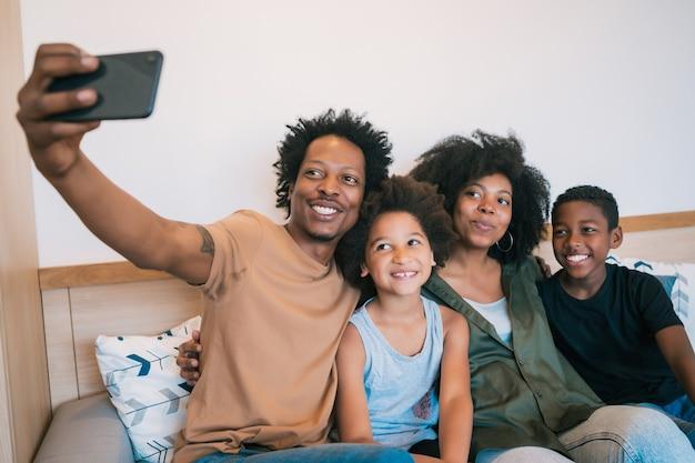 Portret van een familie die een selfie samen met mobiele telefoon thuis neemt