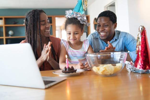 Portret van een familie die online haar verjaardag viert tijdens een videogesprek terwijl ze thuis blijft