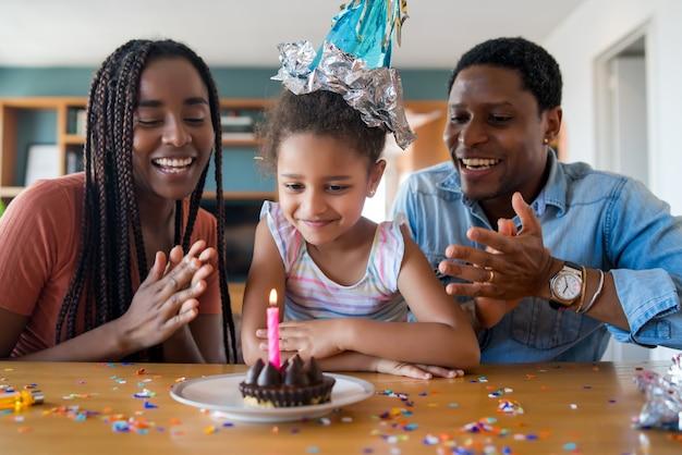 Portret van een familie die online haar verjaardag viert tijdens een videogesprek terwijl ze thuis blijft.