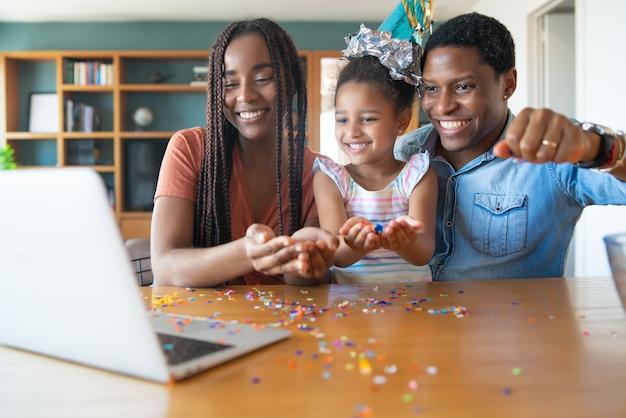 Portret van een familie die online verjaardag viert tijdens een videogesprek met laptop terwijl ze thuis blijven. nieuw normaal levensstijlconcept. Premium Foto