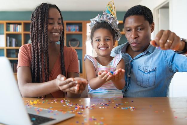 Portret van een familie die online verjaardag viert tijdens een videogesprek met laptop terwijl ze thuis blijven.