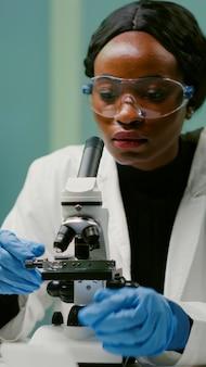 Portret van een farmaceutische vrouw die een glaasje onder de microscoop zet