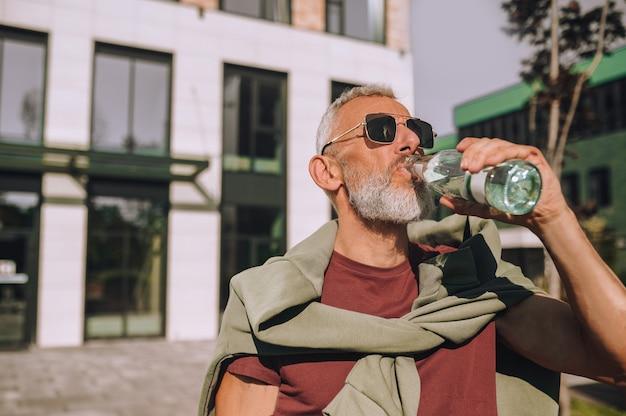 Portret van een fit volwassen mannetje in een zonnebril die water uit de glazen fles buitenshuis drinkt