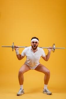 Portret van een fitness man doen oefeningen met zware barbell