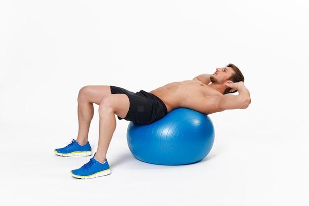 Portret van een fitness man doen rekoefeningen op sportschool