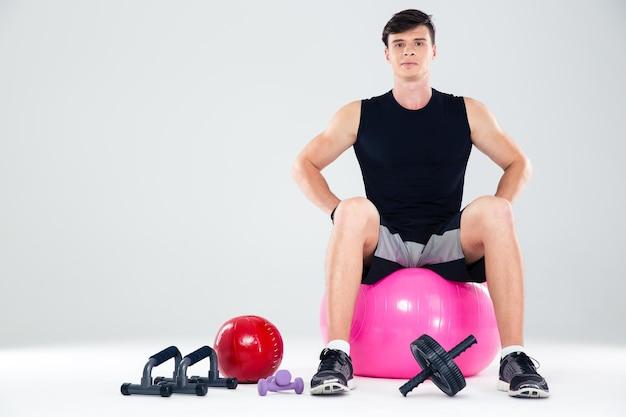 Portret van een fitness man zit op de bal geïsoleerd