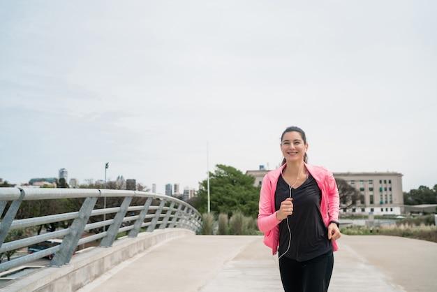 Portret van een fitness-vrouw die buiten in de straat loopt. sport en een gezonde levensstijl concept.