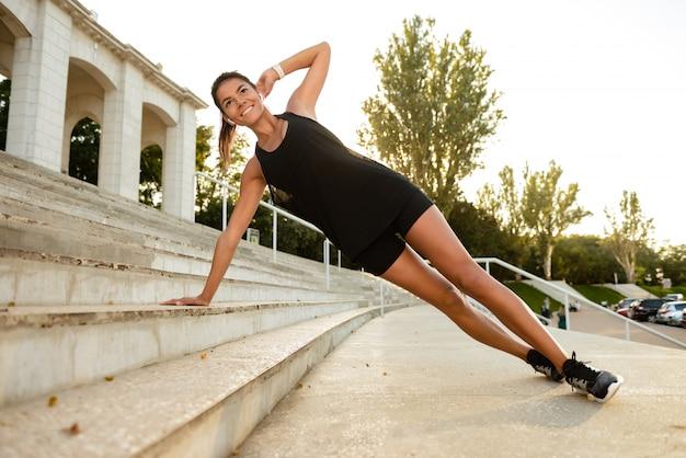 Portret van een fitness vrouw die in oortelefoons sport doet