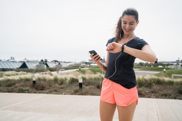 Portret van een fitness-vrouw die tijd controleert op haar slimme horloge. sport en een gezonde levensstijl concept.