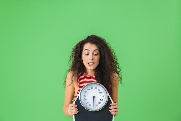 Portret van een fitnessvrouw uit de twintig die zomerkleren draagt met een weegschaal tijdens oefeningen op de groene muur