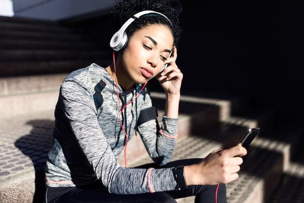 Portret van een fitte en sportieve jonge vrouw die naar muziek luistert met een mobiele telefoon.
