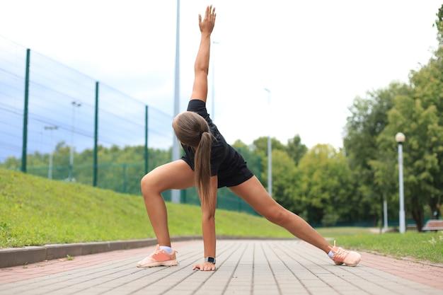 Portret van een fitte en sportieve jonge vrouw die zich buiten uitstrekt.
