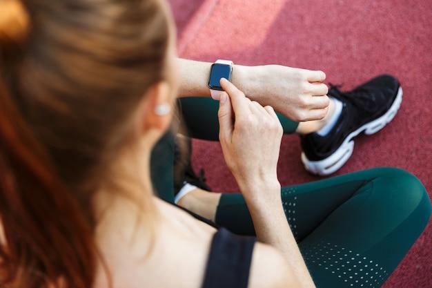 Portret van een fitte jonge vrouw die een trainingspak draagt en naar haar polshorloge kijkt terwijl ze op het sportveld zit tijdens de training in het groene park
