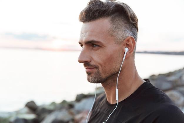 Portret van een fitte sportman, luisteren naar muziek close-up