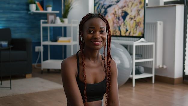 Portret van een fitte zwarte vrouw die in de camera kijkt terwijl ze in lotuspositie zit