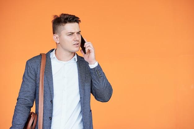 Portret van een fronsende jonge zakenman die telefonisch met een collega praat