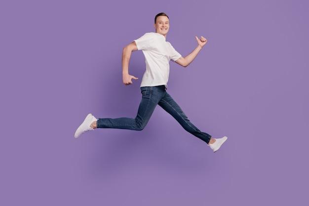 Portret van een funky sportieve man die springt op een paarse achtergrond
