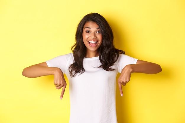 Portret van een geamuseerd afro-amerikaans meisje dat een aankondiging laat zien, glimlachend en met de vingers naar beneden wijst naar gelukkig nieuws, staande over een gele achtergrond.
