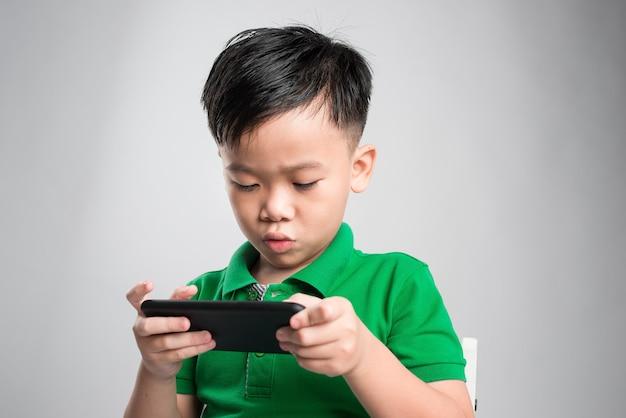 Portret van een geamuseerd schattig klein kind spelen op smartphone geïsoleerd