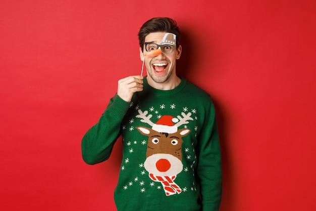 Portret van een geamuseerde knappe man in kersttrui, met een grappig feestmasker en glimlachen, het vieren van wintervakanties, staande op een rode achtergrond