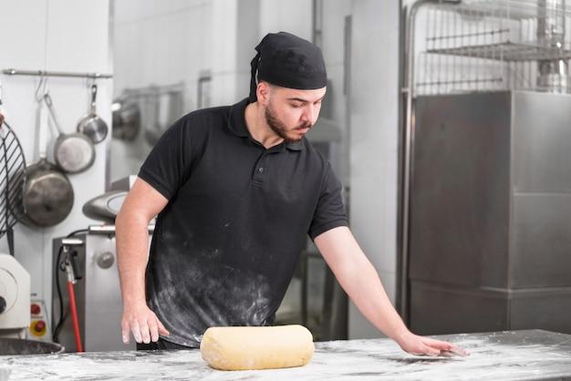 Portret van een gebakjechef-kok in de keuken die wordt voorbereid om het deeg te kneden.