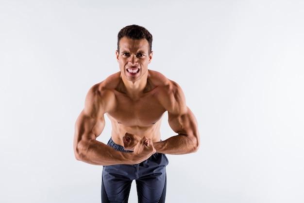 Portret van een gebruinde man die moeite doet om spieren te laten zien