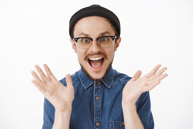 Portret van een gecharmeerde opgewonden knappe bebaarde man die zijn handpalmen opheft en vreugdevol schreeuwt van verbazing en geluk, geïntrigeerd staart terwijl hij goed nieuws hoort