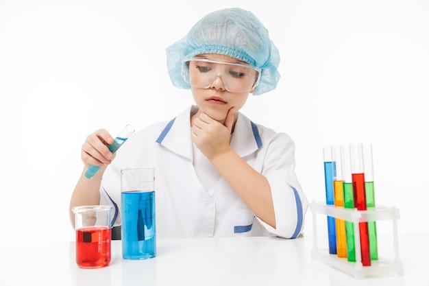 Portret van een geconcentreerd meisje in een witte laboratoriumjas die chemische experimenten maakt met veelkleurige vloeistof in reageerbuizen geïsoleerd over een witte muur