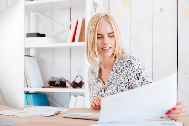 Portret van een geconcentreerde blonde vrouw die door documenten kijkt terwijl ze op de werkplek zit