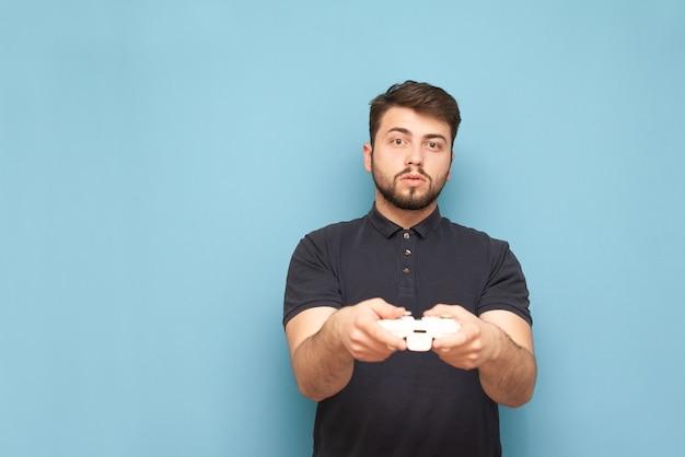 Portret van een geconcentreerde gamer met een joystick in zijn hand op blauw