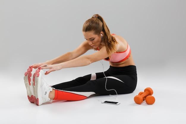 Portret van een geconcentreerde jonge sportvrouw die aan muziek luistert