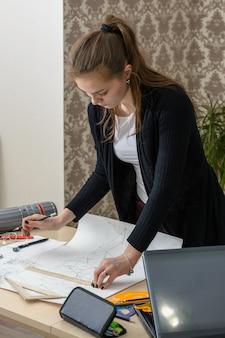 Portret van een geconcentreerde jonge student aan de tafel houdt zich bezig met het tekenen van architectonisch ontwerp